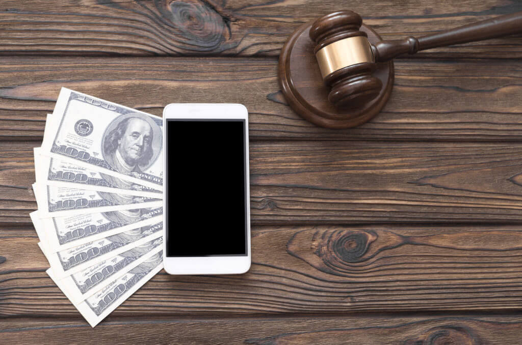 An iPhone sitting on top of a stack of 100-dollar bills next to a gavel on a wooden desk